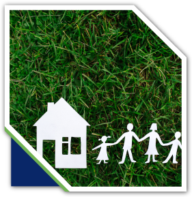 Paper cut out of a family and a house on grass